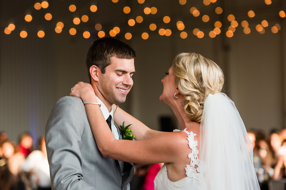 Beautiful first dance spot in the hangar with string lights in the background | Aurora, CO Wedding Photos