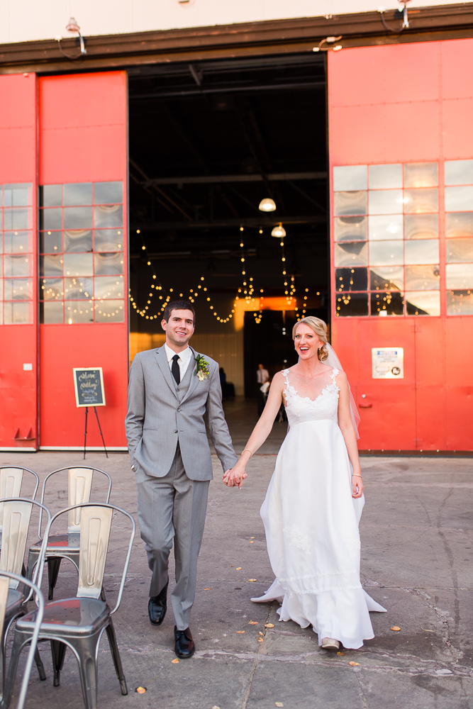 Husband and wife walking away from the big red doors at The Hangar at Stanley Marketplace | Aurora, Colorado wedding photos