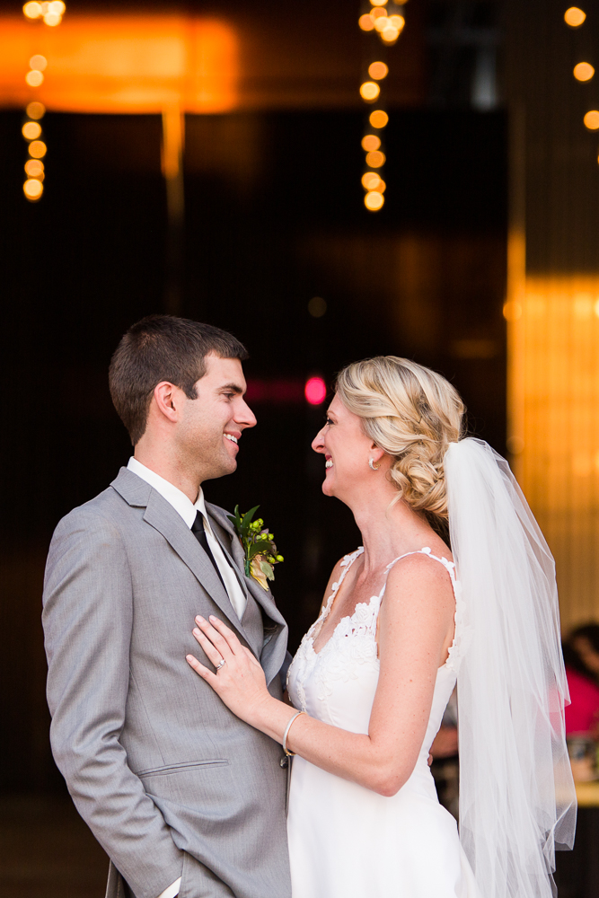 Bride and groom smiling at each other while standing in front of their wedding reception | Aurora, Colorado wedding