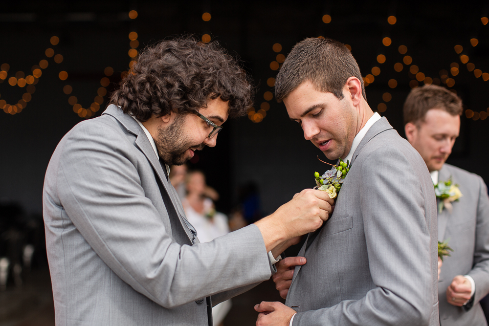 Groomsmen helping groom pin on his boutonniere