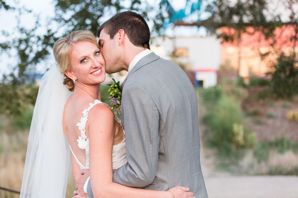 Groom giving bride a kiss on the cheek during golden hour photos on their wedding day in Aurora, CO