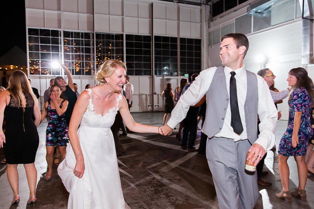 Newly married couple laughing as they walk across the dance floor during their wedding reception at Stanley Marketplace in Aurora, Colorado