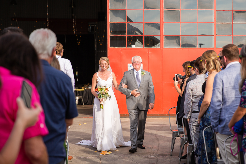 Bride walking down the aisle with her father during wedding ceremony in Aurora, Colorado