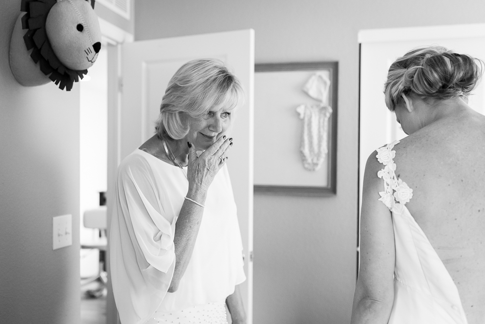 Emotional moment between mother and bride when first seeing her wedding dress