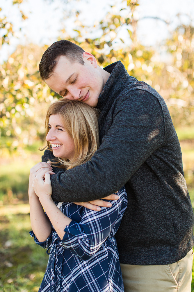 Engaged couple cuddles during a chill fall engagement session