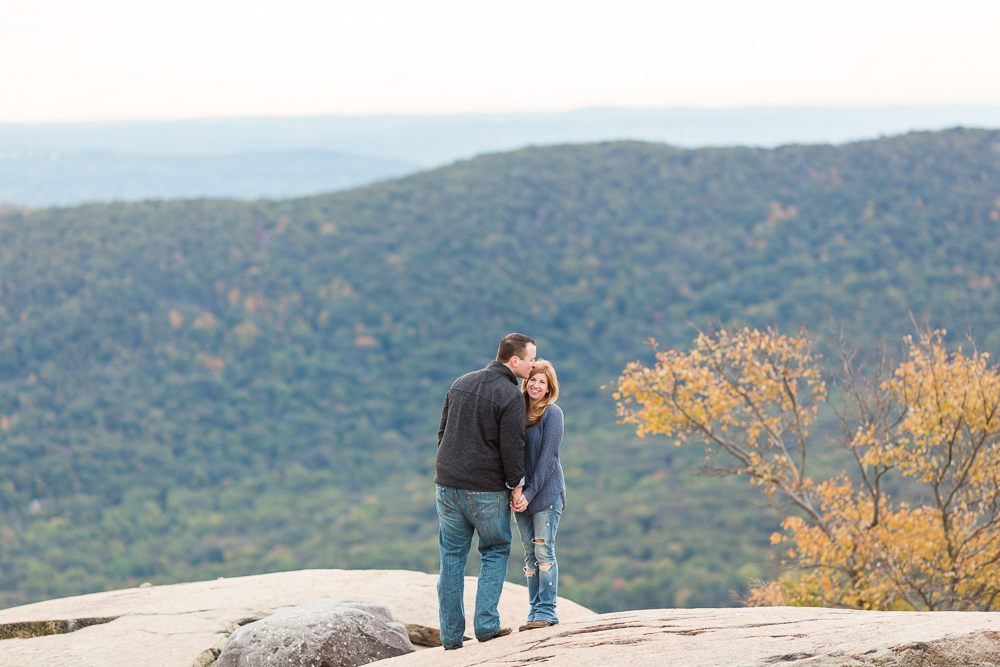 Giving his fiance a kiss on the forehead during a fall engagement session at the top of Bear Mountain, NY