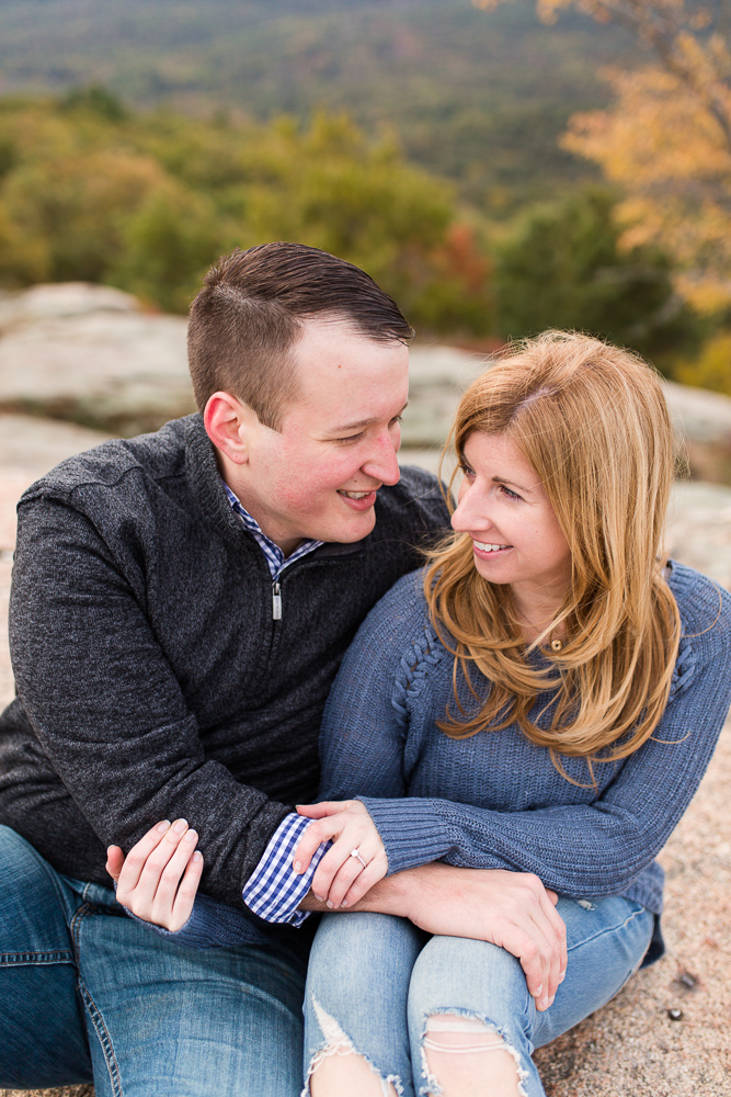 Cuddling close during fall engagement pictures at the top of Bear Mountain   NY engagement photography