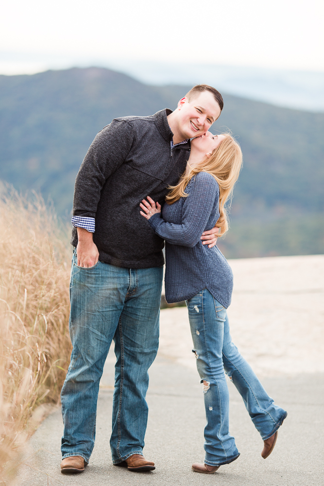 Short bride giving her tall fiance a kiss on the cheek while on tip toes   Bear Mountain NY engagement