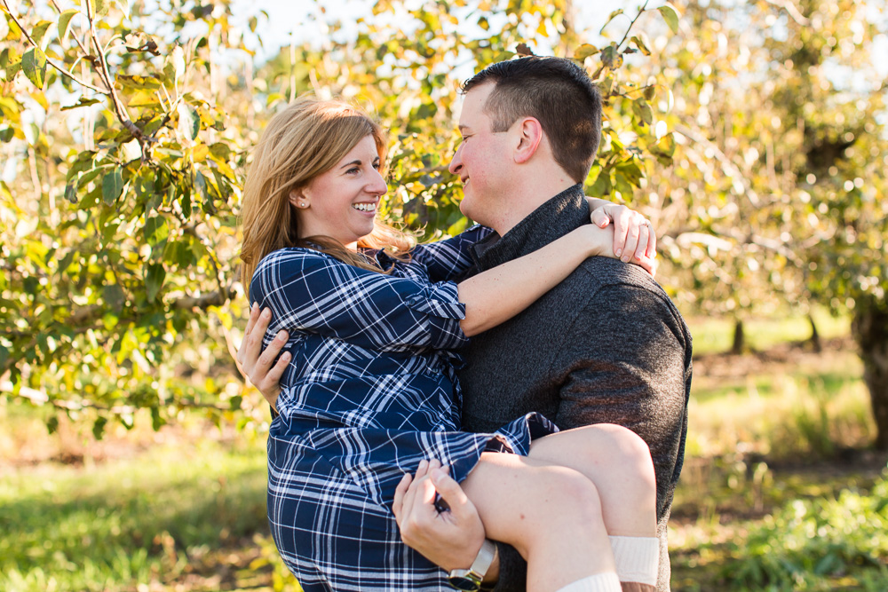 Carrying his fiance through the apple orchard