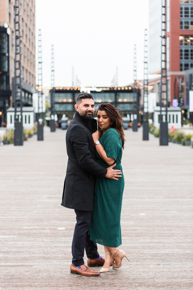 Engaged couple cuddles close on a chilly day after their proposal | District Pier at the DC Wharf