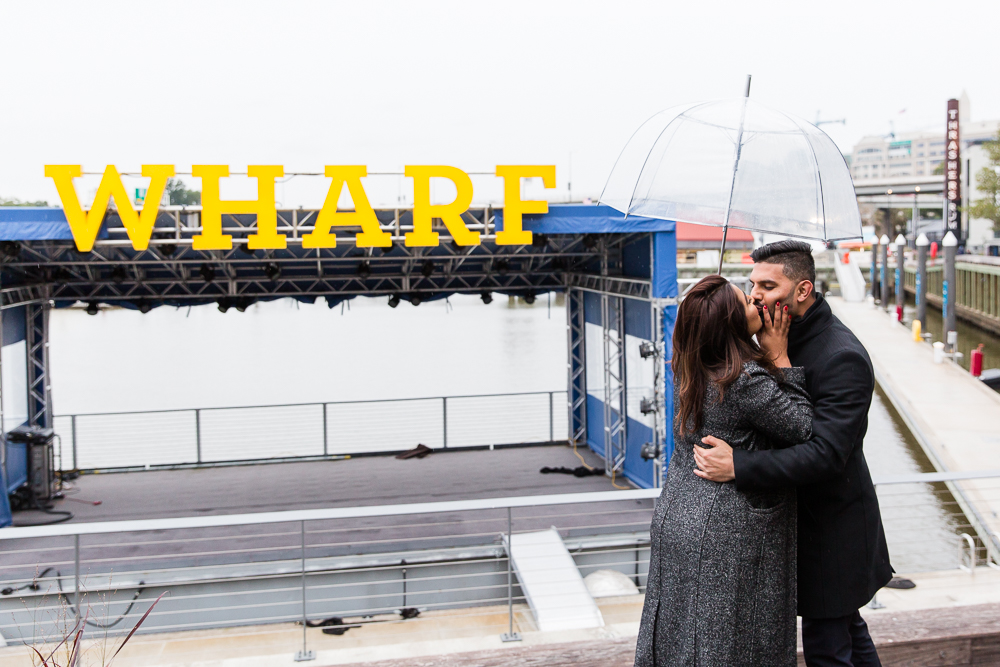 Kissing under an umbrella during a rainy afternoon at the District Wharf | Washington DC engagement session