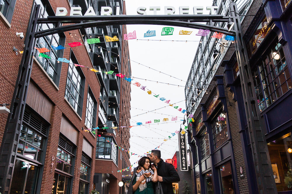 A sweet kiss on the forehead under the colorful prayer flags on Pearl Street of the District Wharf in Washington, DC | DC engagement photography locations