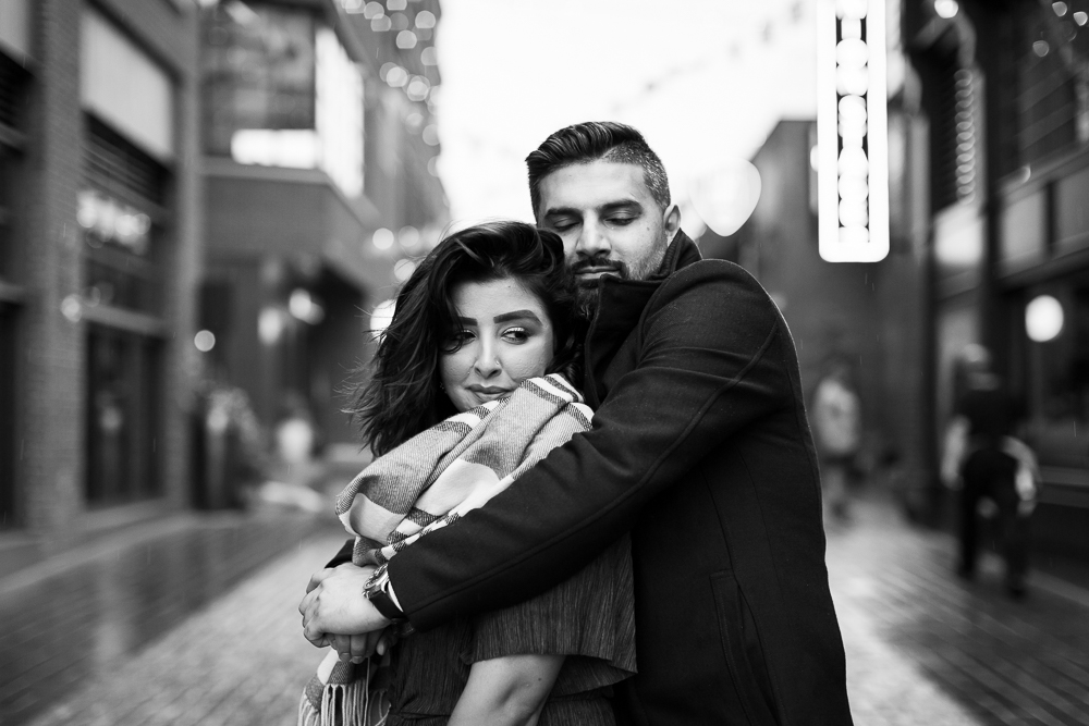 Romantic black and white photo of couple cuddling during a chilly photo shoot at The Wharf