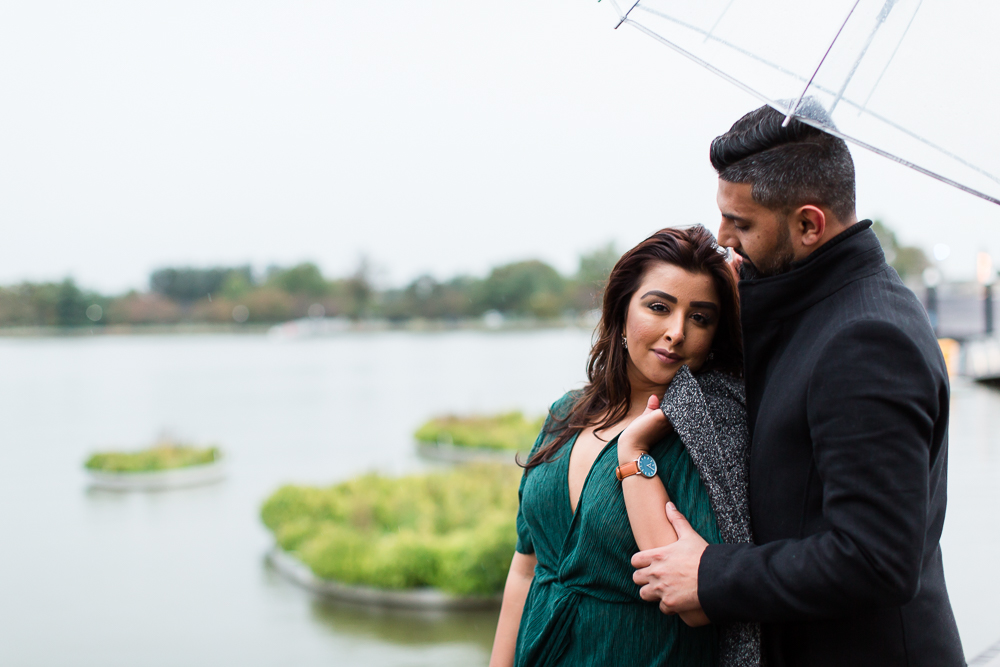 Engaged couple cuddling close during their rainy session at The Wharf