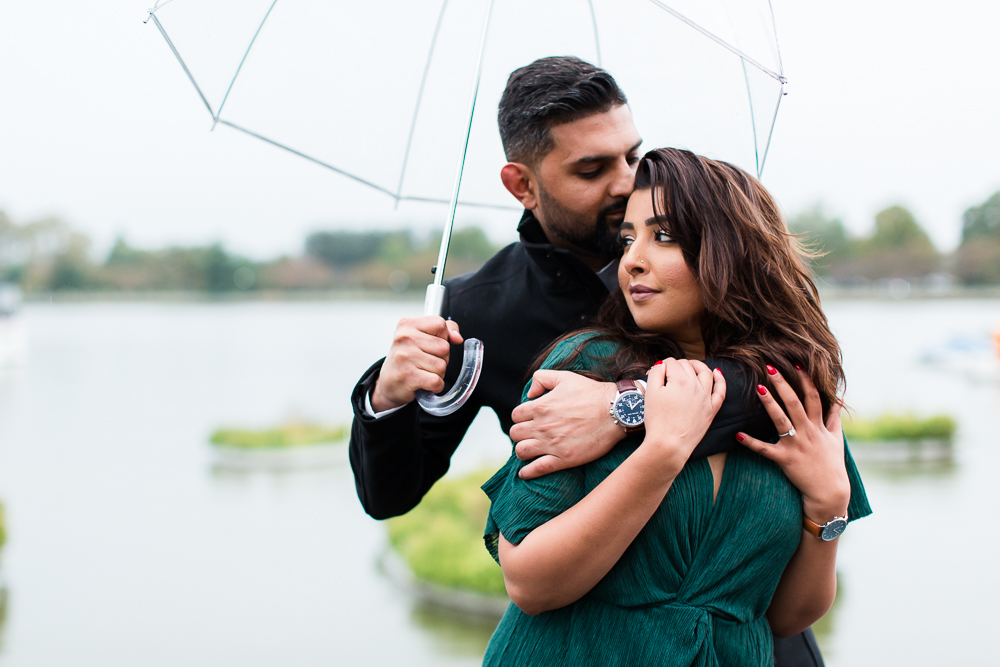 Happy couple by the Potomac River during a rainy photo shoot after their proposal at Wharf DC