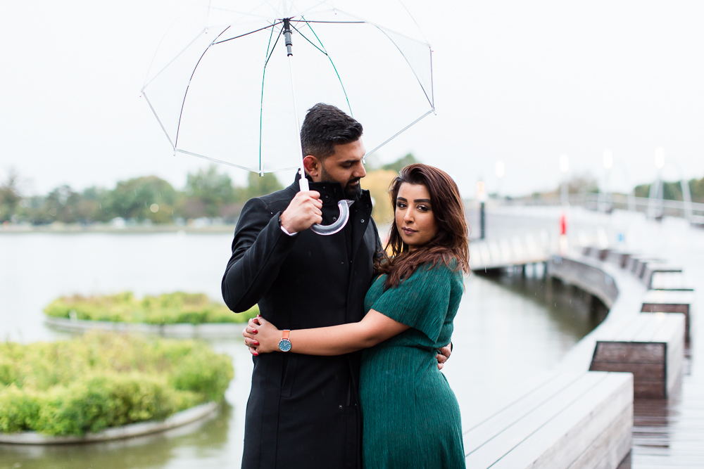 Posing under a clear umbrella for engagement pictures at the pier in DC