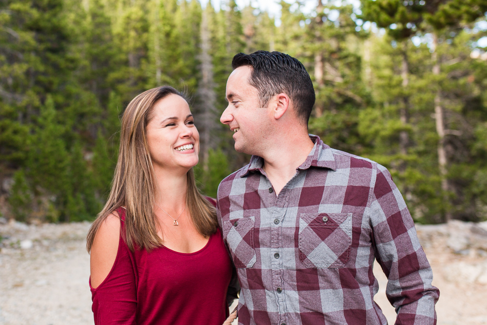 Candid photo of happy couple while hiking | Colorado Engagement Photographer