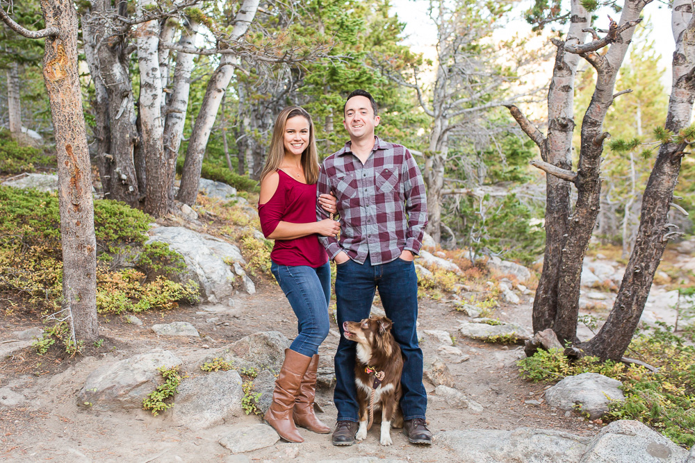 Happy couple with dog standing in between their legs during adventure session on the trails at St. Mary's Glacier | Best adventure engagement spots in Colorado