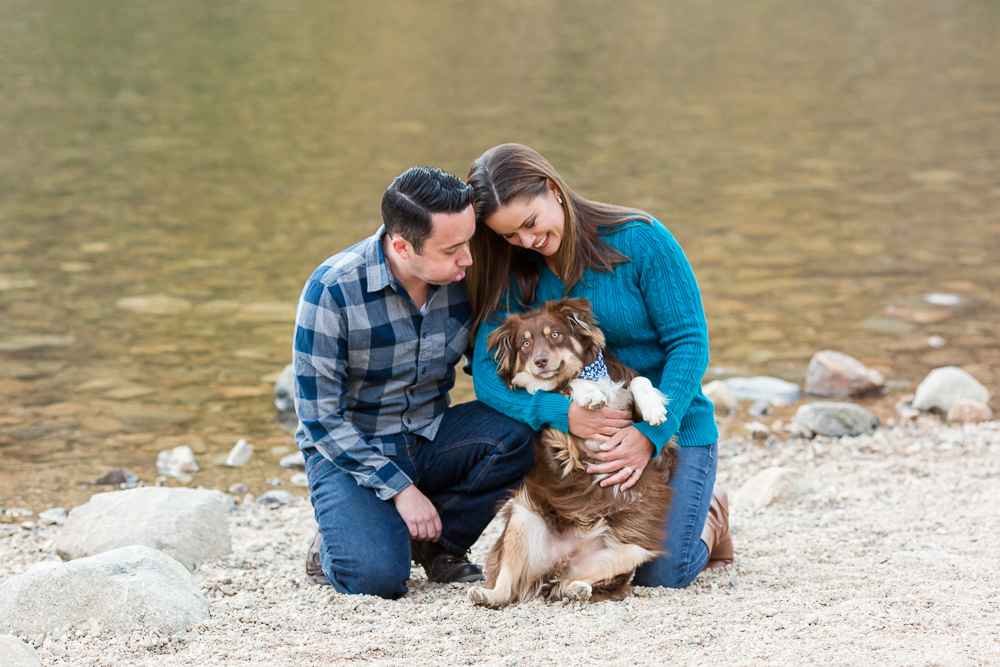 Sweet candid photo of dog parents playing with their miniature Australian shepherd in Idaho Springs, Colorado