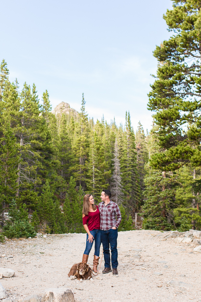 Outdoorsy couple with their dog on a blue sky day in the Colorado mountains