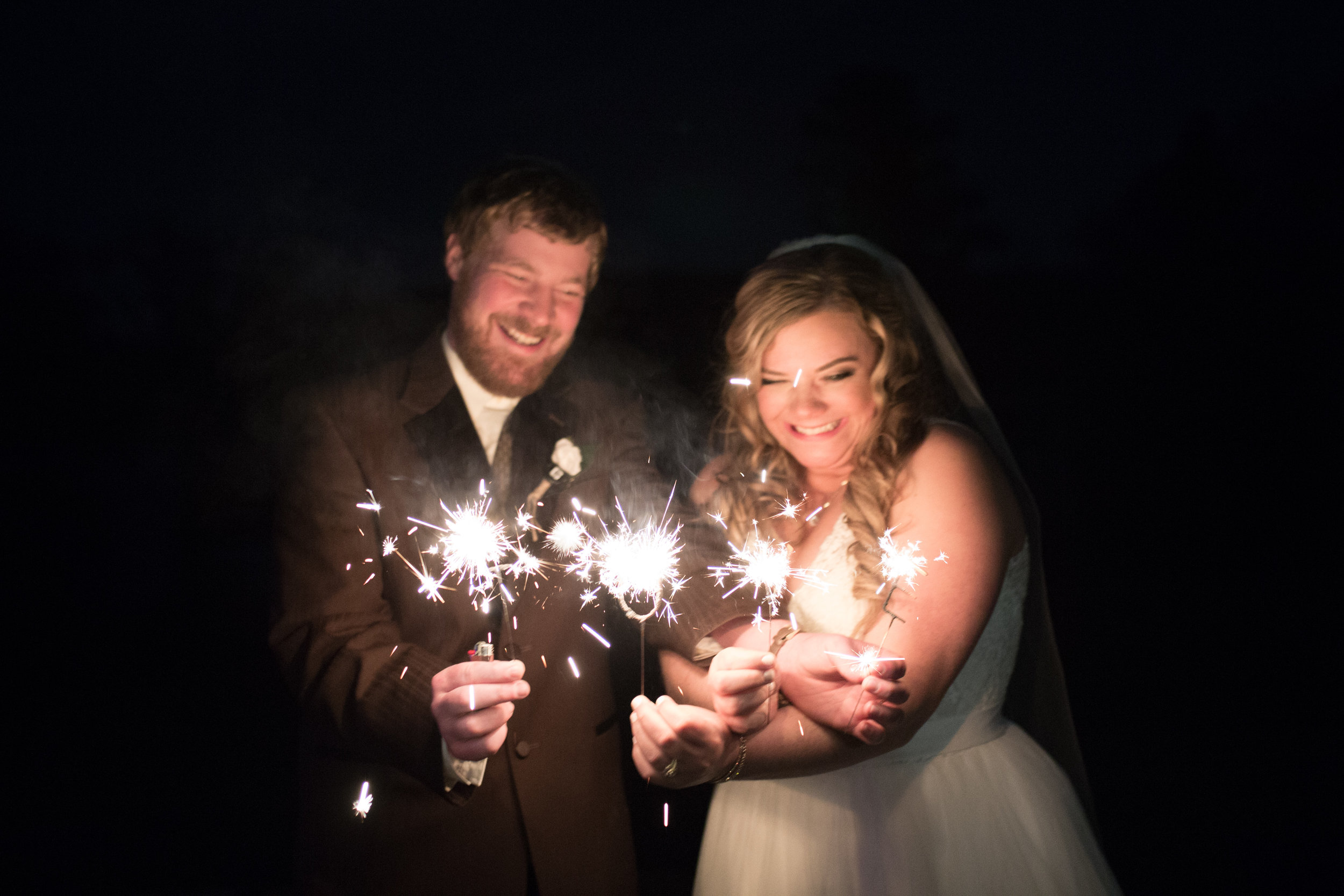 Bride and groom holding LOVE sparklers on their wedding day
