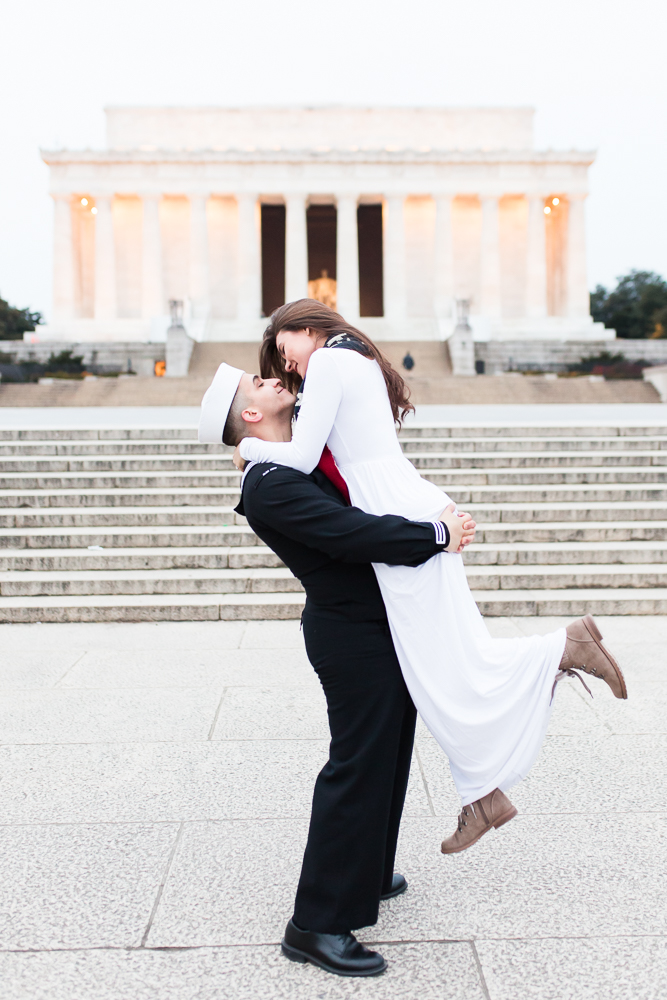 Military groom lifting his bride for wedding pictures in front of the Lincoln Memorial in Washington, DC