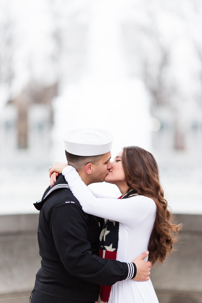 Married couple kissing in front of the fountain at the World War II Memorial in Washington, DC
