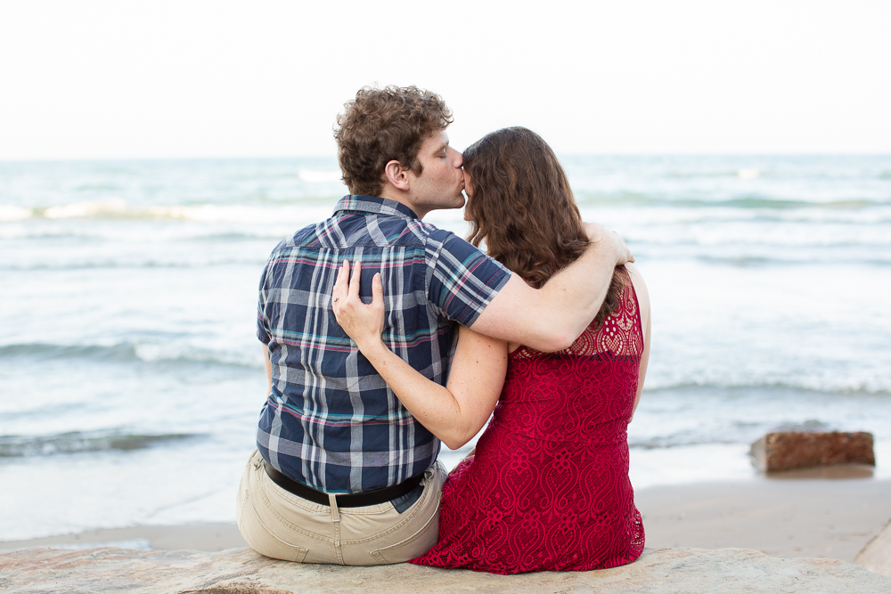 Sweet moment during a beach engagement session | Candid Virginia engagement photographer
