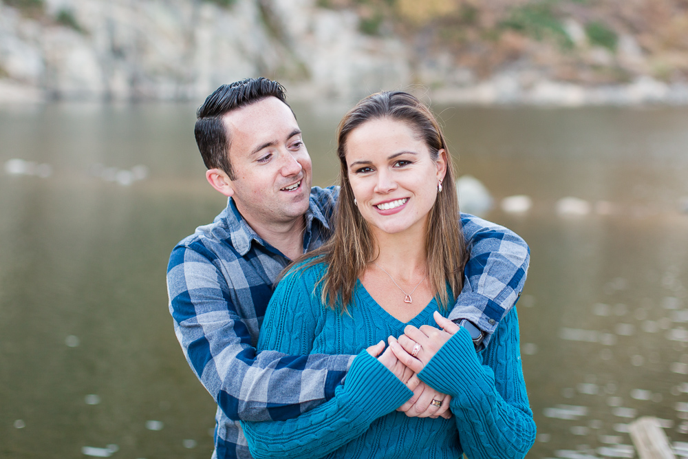 Engaged couple smiling as they pose in front of a lake | Northern Virginia engagement photography