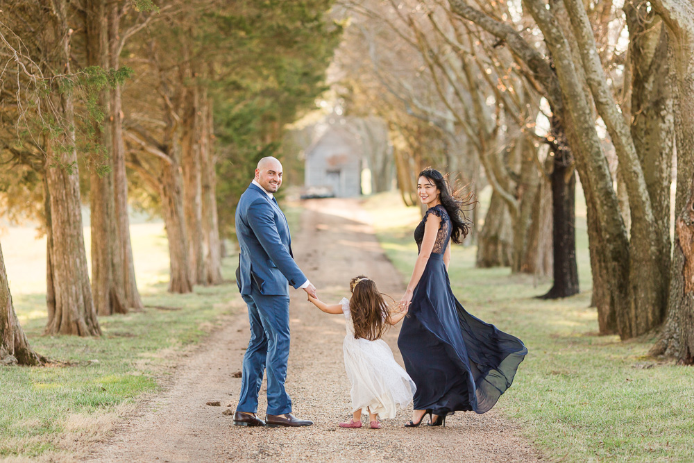 Engaged couple walking down the dirt, tree-lined path with their daughter