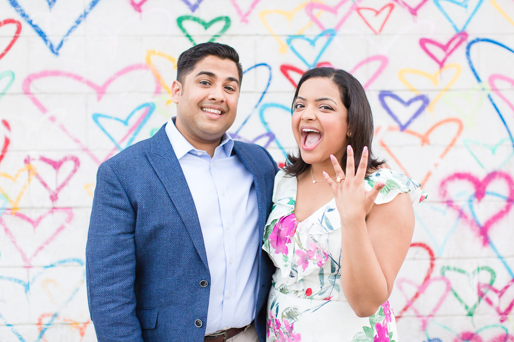 Fun engagement picture in front of the heart wall at Union Market | Fun DC engagement photographer