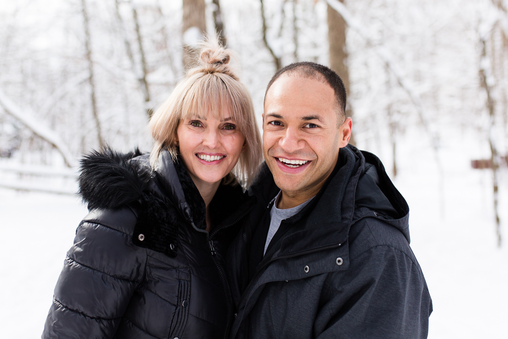 Smiling engaged couple during their winter pictures on the Reston trail system