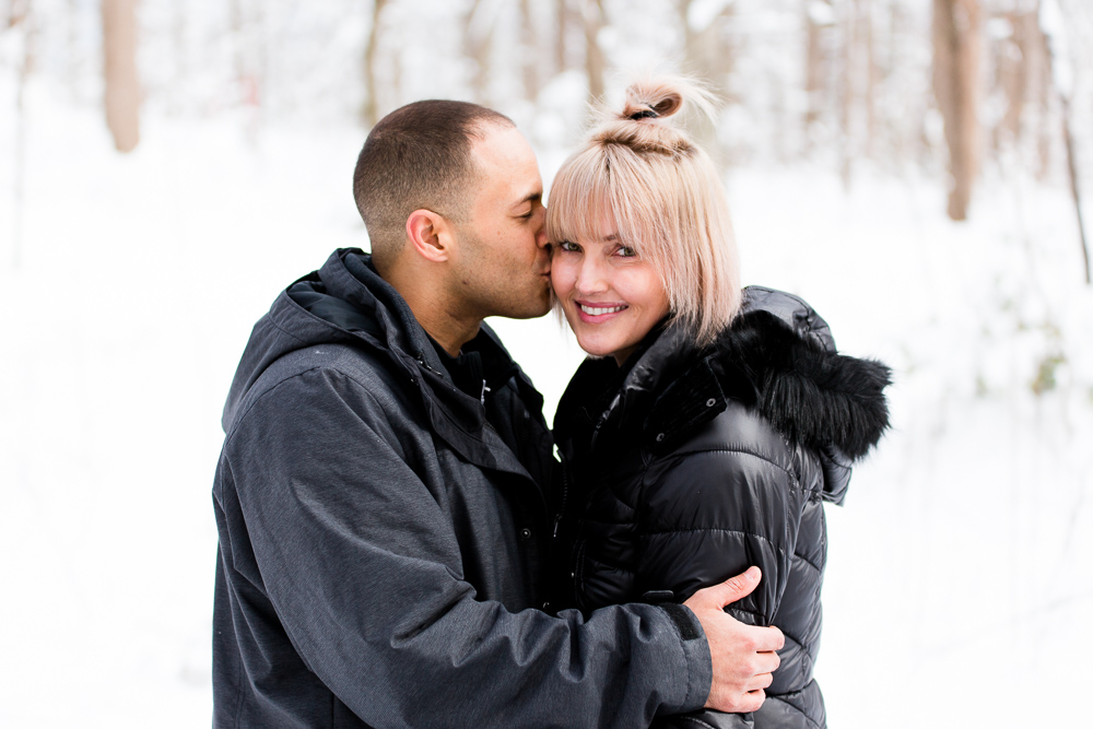 Giving his fiance a kiss on the cheek during a snowy engagement | Washington, DC winter engagement pictures