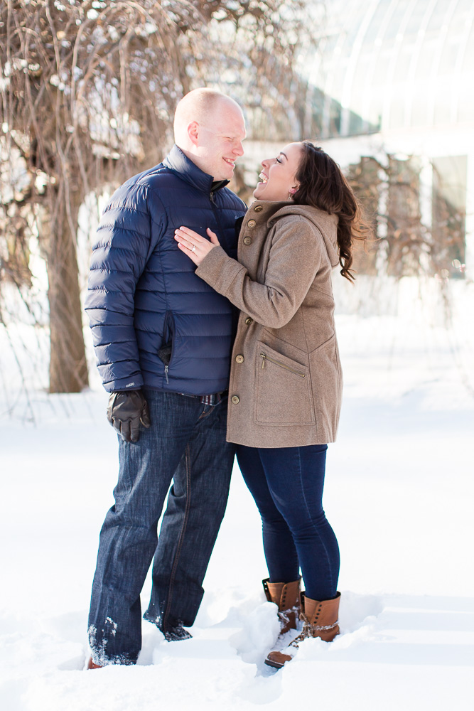 Happy couple in the snow during their winter engagement session at Highland Park