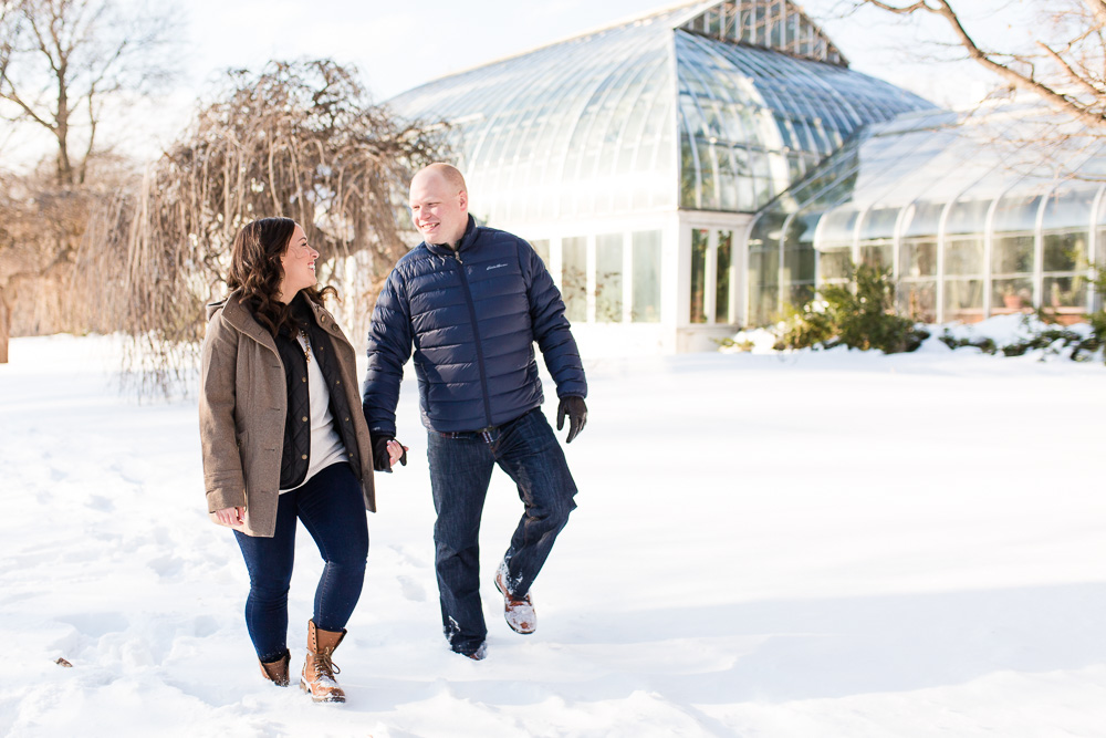 Engaged couple holding hands in front of the Lamberton Conservatory at Highland Park in Rochester, NY | Rochester engagement ideas