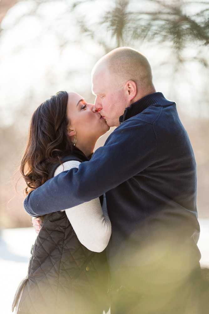 Couple shares a kiss in the snow during their engagement session