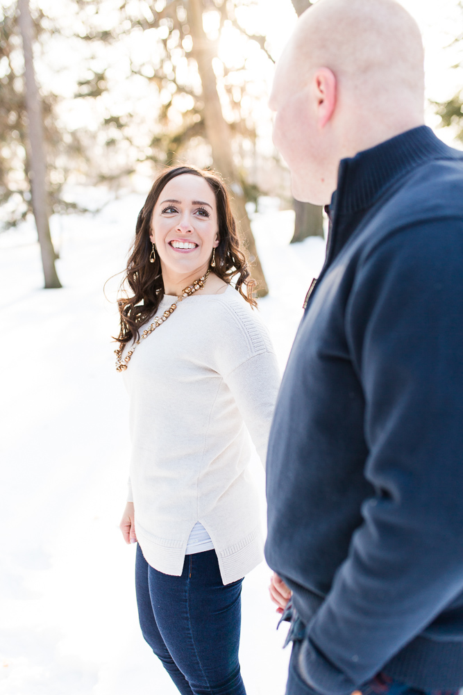 Bride-to-be smiling at her future husband as they walk through the snow