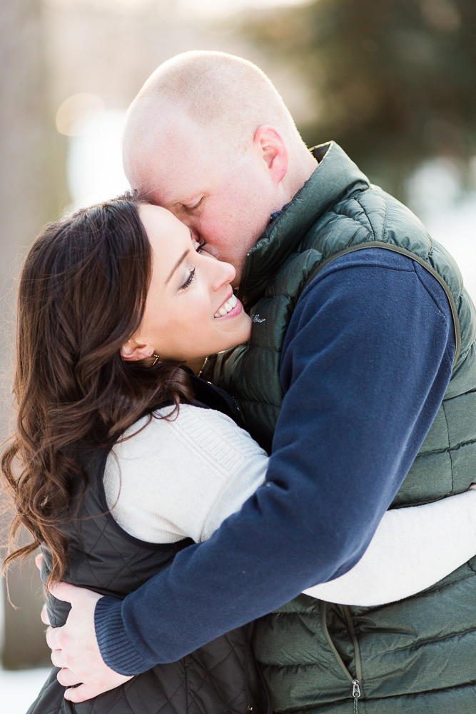 Groom-to-be giving his fiancee a kiss on the cheek during their chilly winter engagement session in Rochester, New York