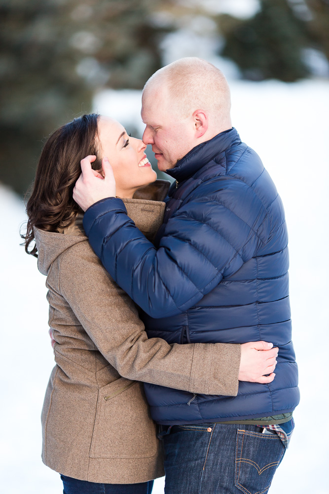Couple leaning in for a kiss during a snowy photo session in Rochester, NY