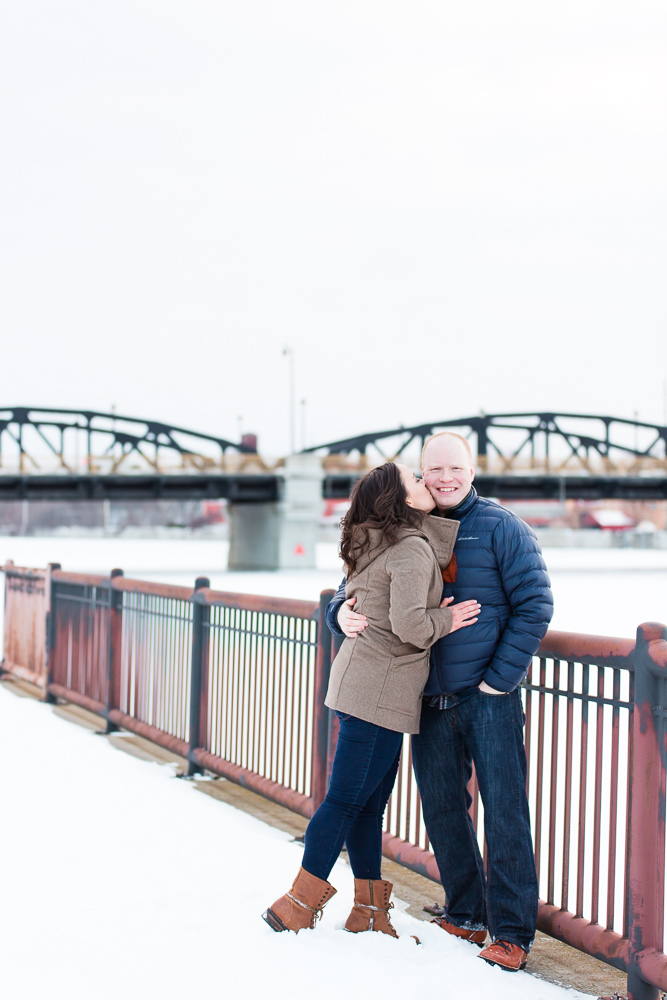 Giving her fiance a kiss on the cheek as they stop along the Genesee River during a winter engagement session | Rochester, NY winter engagement