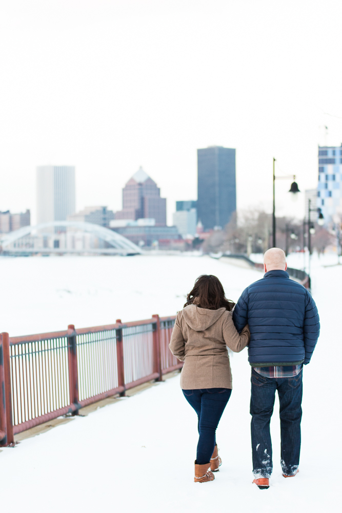 Engaged couple walking arm-in-arm along the Genesee River Trail during a winter engagement shoot in Rochester, NY