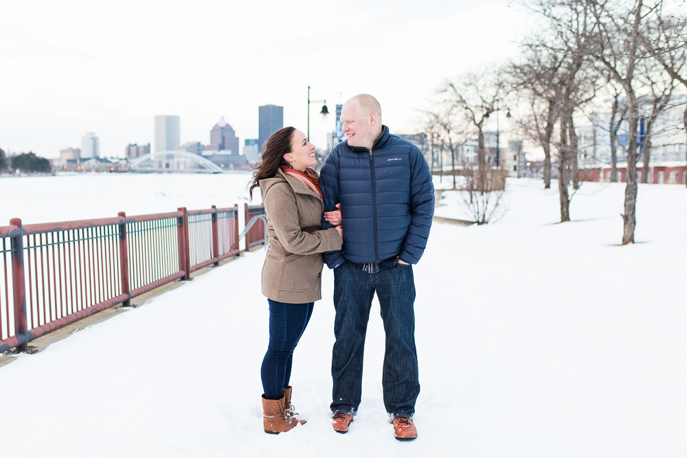 Happy couple smiling despite the cold during their winter engagement pictures in the South Wedge, with downtown Rochester, NY skyline