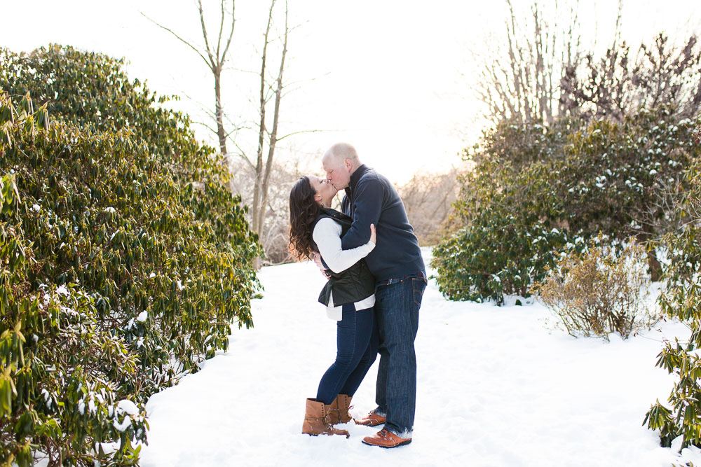 A kiss on the reservoir trails at Highland Park in Rochester, NY during a winter engagement shoot