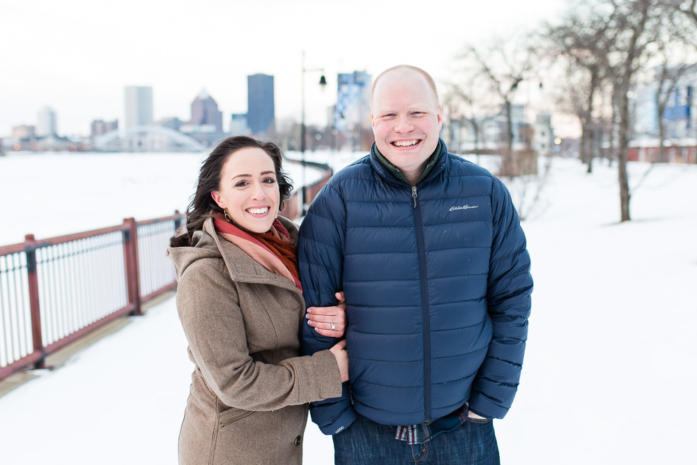 Winter engagement pictures by the Genesee River with Rochester skyline in the background