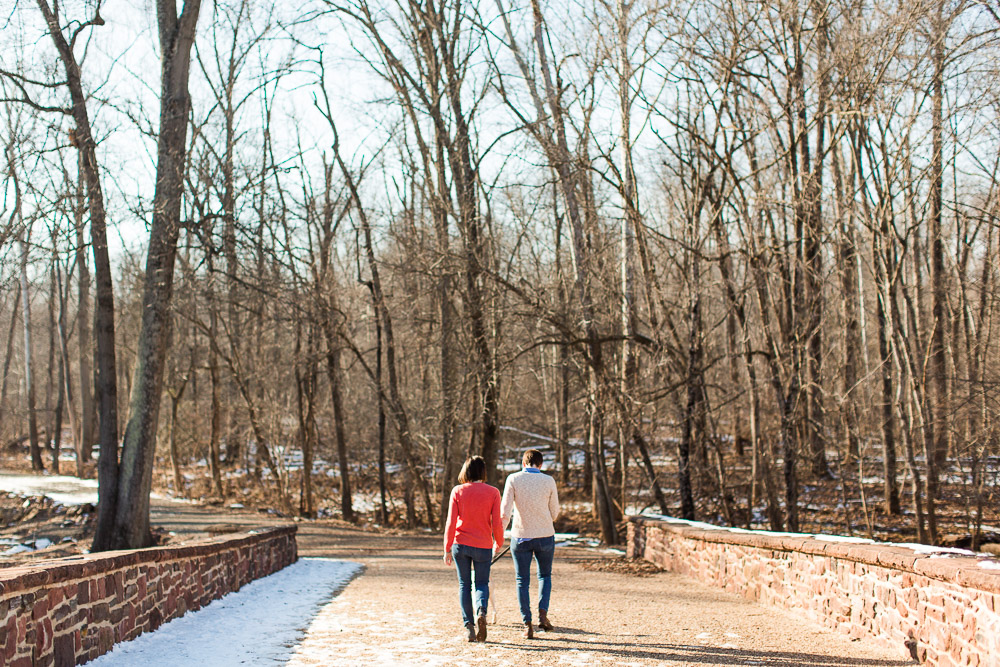 Engaged couple walking across the Stone Bridge during winter engagement photos at Manassas National Battlefield Park