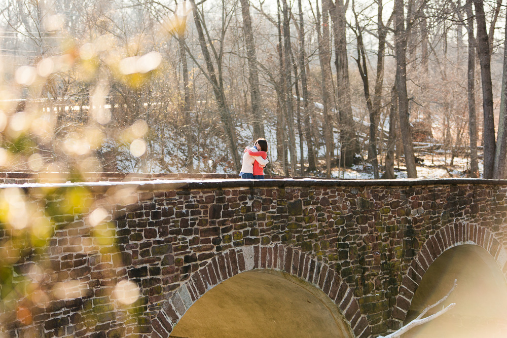 Engaged couple hugging on the Stone Bridge at Manassas Battlefield Park | Manassas engagement pictures