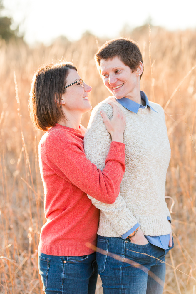 Couple smiling at each other in the tall grass during golden hour at Manassas National Battlefield Park in Northern Virginia