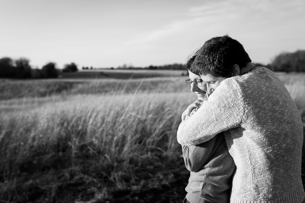 Black and white picture of same-sex couple hugging in Manassas Battlefield | Northern Virginia engagement photographer