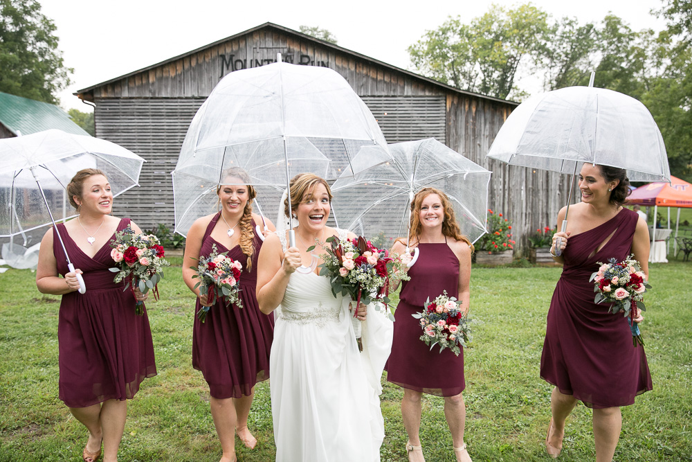 Bride and bridesmaids under clear umbrellas on a rainy wedding day | How to have fun when it rains on your wedding day