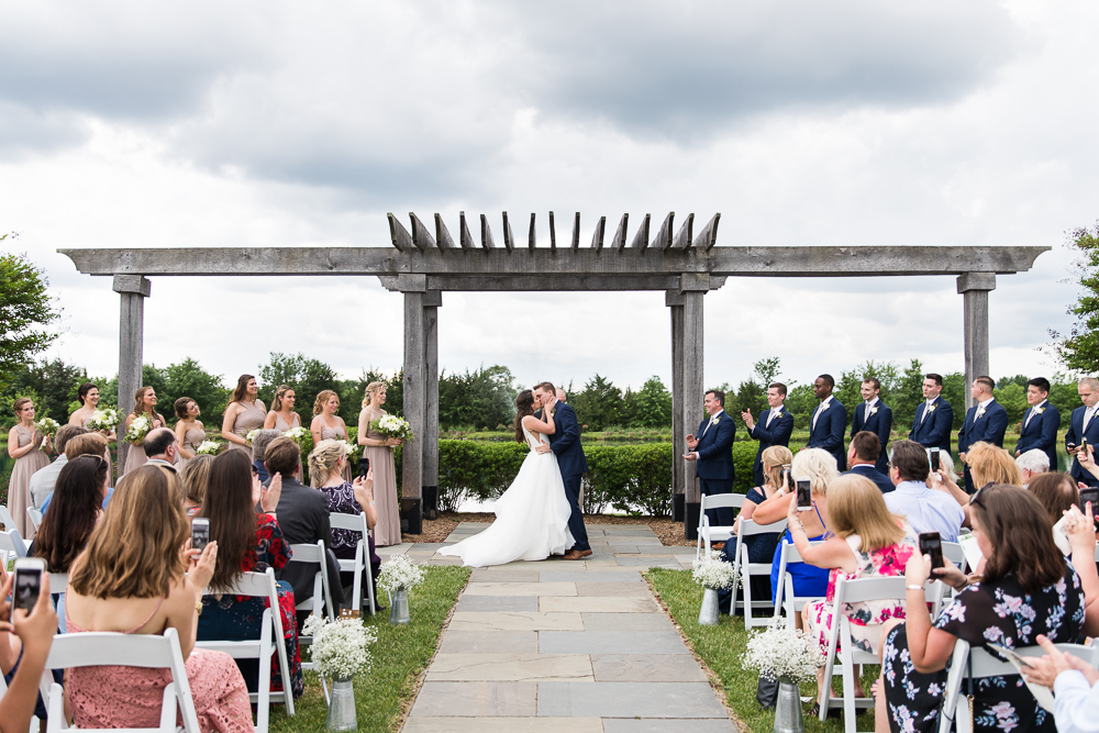 Outdoor wedding ceremony with storm clouds rolling in | What to do when it rains on your wedding day